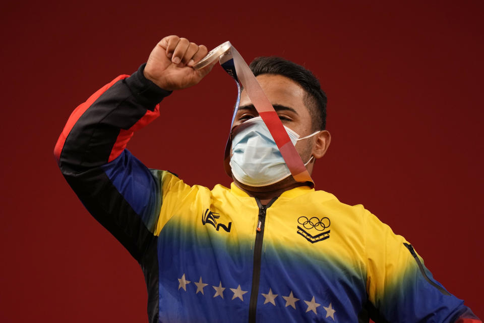 Keydomar Giovan Vallenilla Sanchez of Venezuela celebrates after winning the silver medal in the men's 96kg weightlifting event, at the 2020 Summer Olympics, Saturday, July 31, 2021, in Tokyo, Japan. (AP Photo/Luca Bruno)