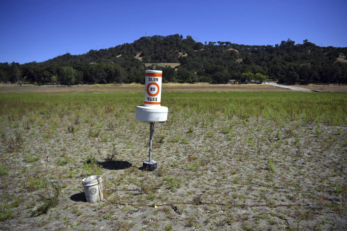 A buoy sits on dry land that had been under water, at a drought-stricken Lake Mendocino, currently at 29% of it normal capacity, in Ukiah, Calif., on Sunday, May 23, 2021. California Gov. Gavin Newsom declared a drought emergency for most of the state. (AP Photo/Josh Edelson)