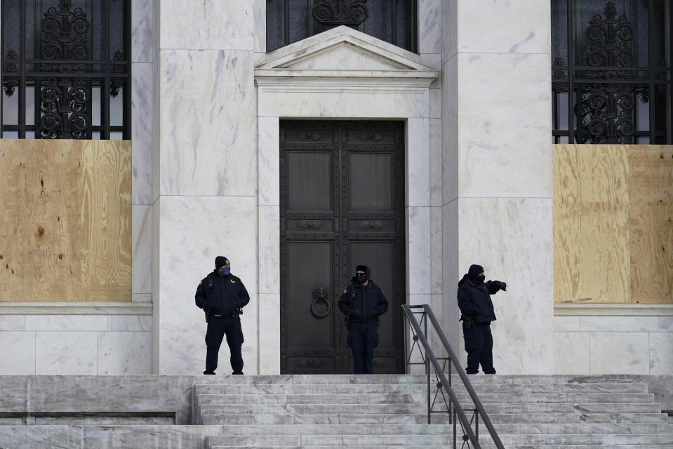 Security guards stand in front of a boarded Federal Reserve building ahead of President-elect Joe Biden's inauguration ceremony, Wednesday, Jan. 20, 2021, in Washington. (AP Photo/Gerald Herbert)