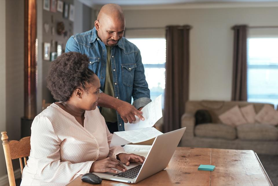 middle-aged black couple paying bills