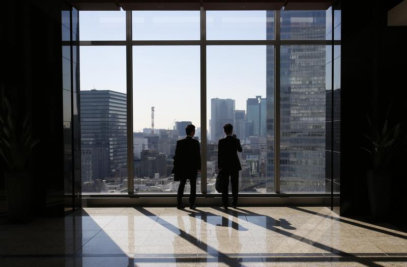 Businessmen are seen inside a high-rise office building in Tokyo