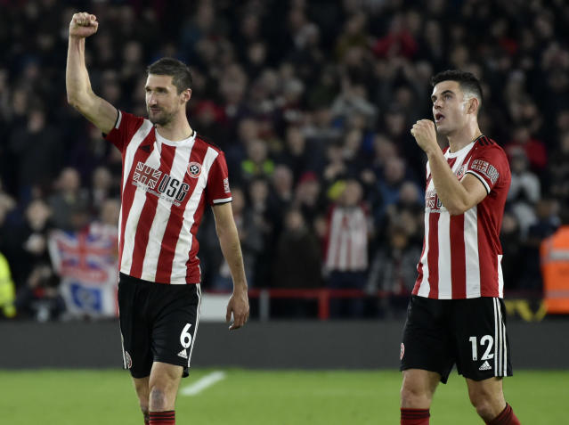 Sheffield United's Chris Basham, left, and John Egan celebrate after they won the English Premier League soccer match between Sheffield United and Arsenal at Bramall Lane in Sheffield, England, Monday, Oct. 21, 2019. (AP Photo/Rui Vieira)