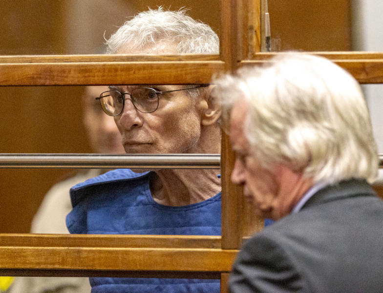 Edward Buck listens to his defense attorney Seymour Amster, right, during an appearance in Los Angeles Superior Court, Thursday, Sept. 19, 2019, in Los Angeles. The prominent LGBTQ political activist was arrested Tuesday and charged with operating a drug house and providing methamphetamine to a 37-year-old man who overdosed on Sept. 11, but survived, officials said. Two other men have died in his apartment since 2017. (AP Photo/Damian Dovarganes)