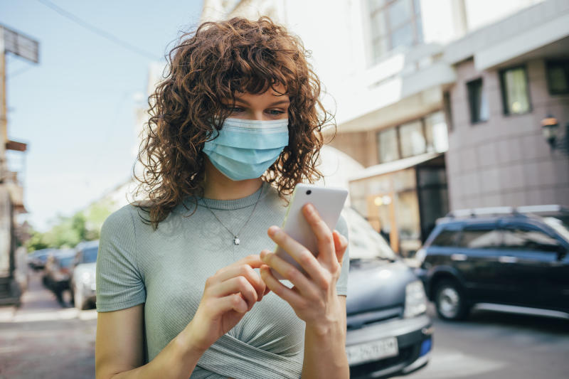 Woman wearing protective mask and using smartphone in city