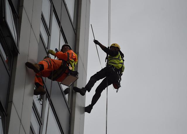 <p>Specialists abseil down the side of Bray Tower to check the cladding, on the Chalcots Estate in north London, Britain, June 27, 2017. (Photo: Hannah McKay/Reuters) </p>