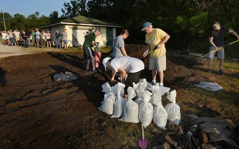 St Johns County Florida residents wait for the arrival of sandbags at Mills Field - Credit: Bob Self/The Florida Times-Union via AP