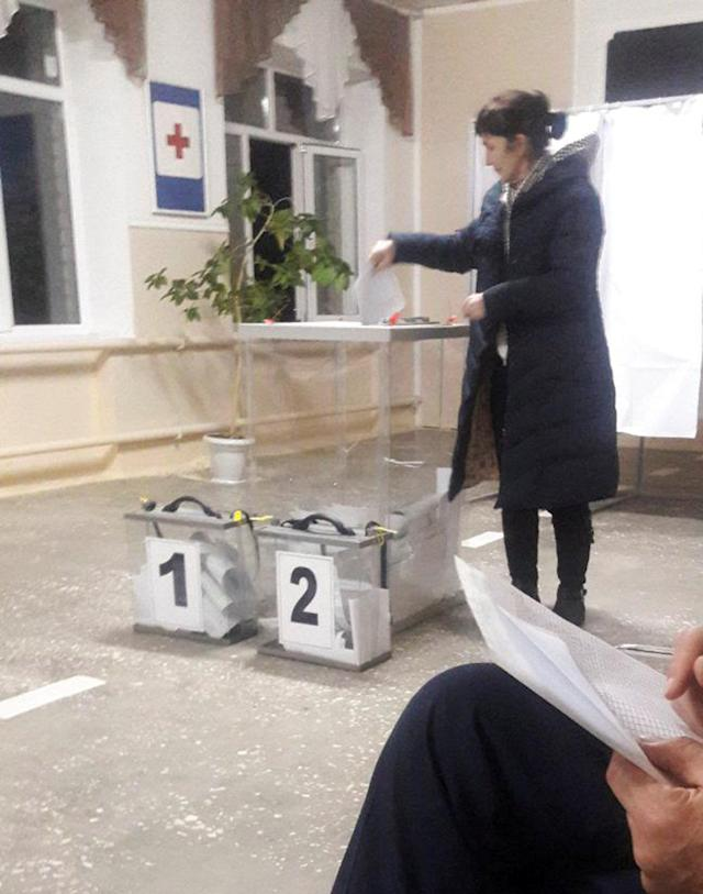 A voter casts a ballot at a polling station number 215 during the presidential election in Ust-Djeguta, Russia March 18, 2018. The voter denied voting multiple times to a Reuters reporter and said it was a case of mistaken identity because seven people at her work have the same coat. Picture taken March 18, 2018. REUTERS/Polina Nikolskaya