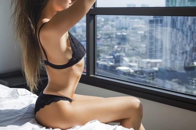 Sexy woman wearing black lingerie sitting on the bed
