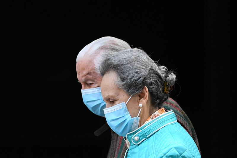 An elderly couple wearing face masks walks in Madrid on April 30, 2020 during a national lockdown to prevent the spread of the COVID-19 disease. - Spain counted another 268 people who have died from the coronavirus, the lowest daily number since March 20 as the country prepares to ease its tough lockdown measures. (Photo by Gabriel BOUYS / AFP) (Photo by GABRIEL BOUYS/AFP via Getty Images)