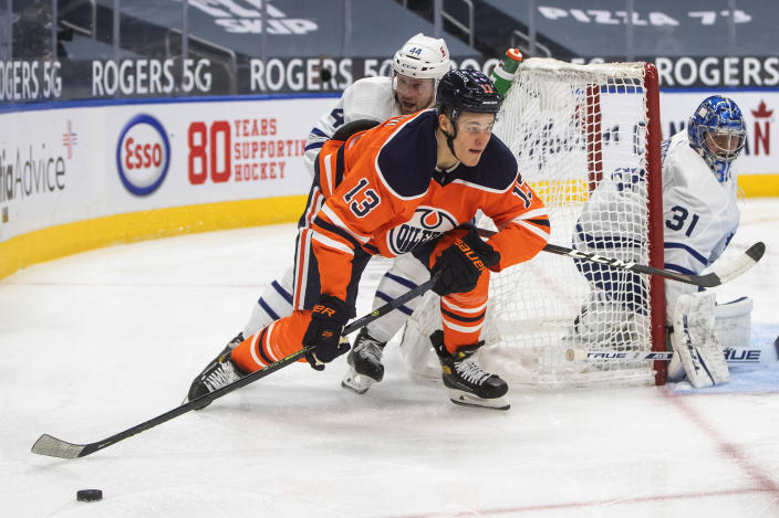 Edmonton Oilers' Jesse Puljujarvi (13) and Toronto Maple Leafs' Morgan Rielly (44) work for the puck during the second period of an NHL hockey game Wednesday, March 3, 2021, in Edmonton, Alberta. (Jason Franson/The Canadian Press via AP)