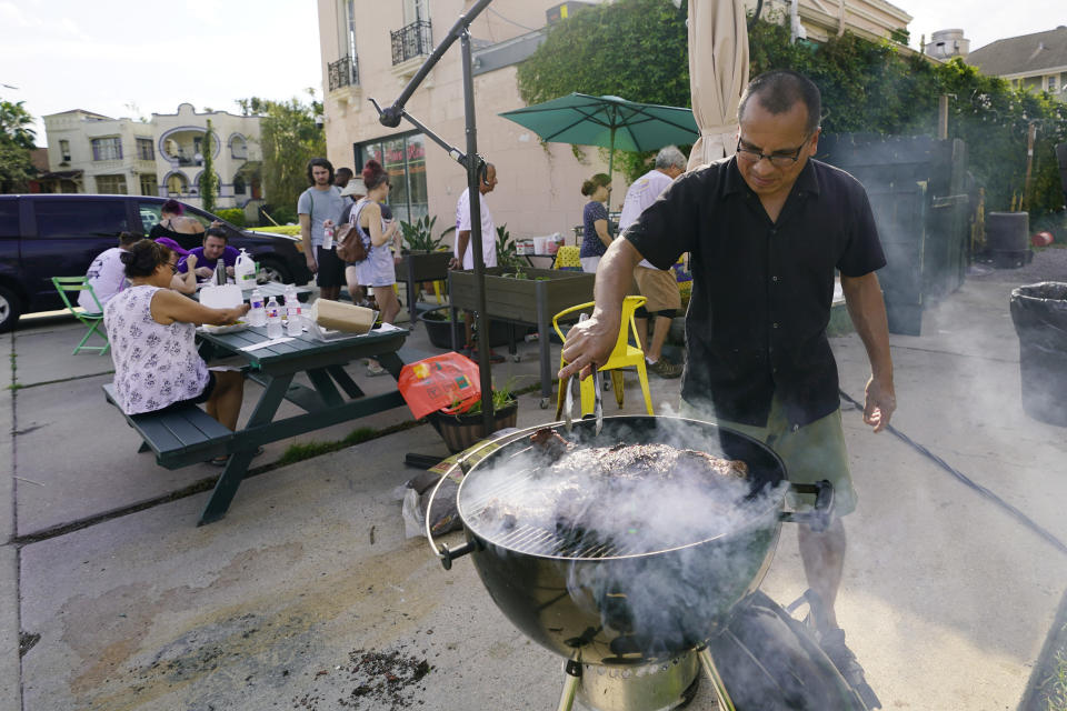 In this Wednesday, Sept. 1, 2021, photo, Mario Aranda grills steak at El Pavo Real restaurant where they served up a free steak taco meal, in New Orleans, La. In New Orleans, food is just one of the many ways that residents help each other during hard times. And it's been no different in the days after Hurricane Ida, which flooded or destroyed homes, tore up trees and knocked out the entire city's power grid.(AP Photo/Eric Gay)