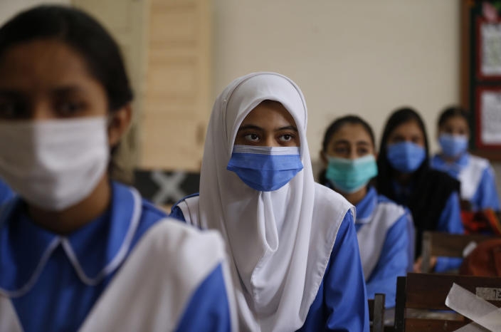 Students wearing face masks to prevent the spread of coronavirus, attend a class at a school, in Islamabad, Pakistan, Tuesday, Sept. 15, 2020. Pakistani officials welcomed millions of children back to school following educational institutions reopened on Tuesday in the country amid a steady decline in coronavirus deaths and infections. (AP Photo/Anjum Naveed)