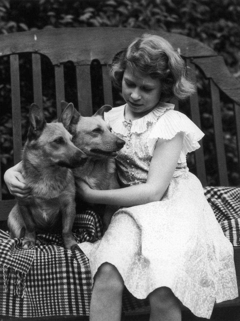 """<p>Queen Elizabeth has adored Corgis ever since she was a little girl, so much so that the royal was known to <a href=""""https://www.romper.com/p/why-does-queen-elizabeth-ii-like-corgis-theyve-been-in-the-family-for-nearly-80-years-9275552"""" rel=""""nofollow noopener"""" target=""""_blank"""" data-ylk=""""slk:breed them at Buckingham Palace"""" class=""""link rapid-noclick-resp"""">breed them at Buckingham Palace</a>. Here, the young princess is seen with two of her family pets, Jane and Dookie. </p>"""