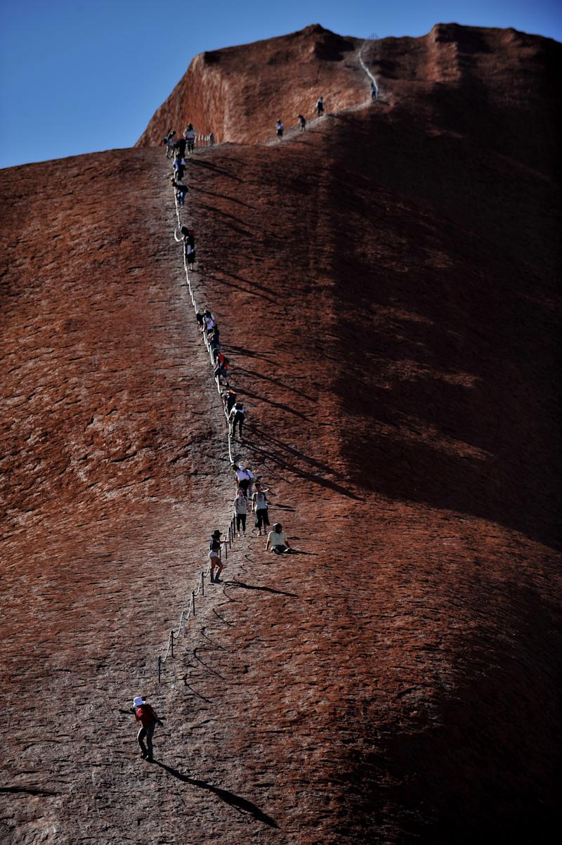 Pictured are dozens of tourists descending Uluru in the Northern Territory in 2010.