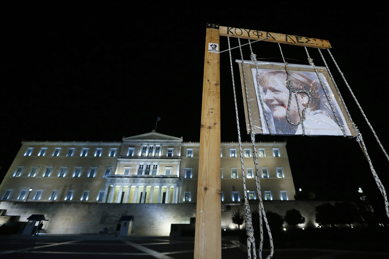 A picture of German Chancellor Angela Merkel symbolically hangs from a gibbet in front of the Parliament. The writing on the noose reads in Greek: 'Rascals'.