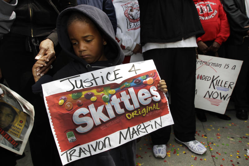 "FILE - In this March 27, 2012 file photo, Steven Jonhson, 3, holds an enlarged banner of ""Skittles"" candy, as he joins Los Angeles community members at a ""Justice for Trayvon Martin hoodie rally"" in honor of Trayvon Martin, the unarmed black teenager who was wearing a hoodie on the night when he was shot and killed by a neighborhood watch captain George Zimmerman. Skittles isn't the first popular food brand to find itself at the center of a major controversy. The terms ""the Twinkie defense"" and ""don't drink the Kool-Aid"" became part of the vernacular decades ago in the wake of tragic events. More recently, Doritos made headlines when it was reported that the corn chips were Saddam Hussein's favorite snack. (AP Photo/Damian Dovarganes, File)"