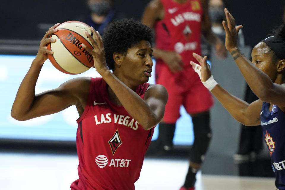 Angel McCoughtry, in a red Aces jersey, holds the ball back behind her head against the defense.