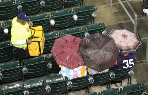 A vendor makes his way through baseball fans as they wait out a rain delay before a baseball game between the Minnesota Twins and the Detroit Tigers at Comerica Park in Detroit, Friday, Sept. 21, 2012. (AP Photo/Carlos Osorio)
