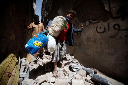 People carry their belongings at the site of an air strike launched by the Saudi-led coalition in Sanaa, Yemen  May 16, 2019. REUTERS/Mohamed al-Sayaghi