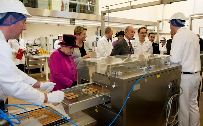 Queen Elizabeth II and the Duke of Edinburgh during a visit to Mars Chocolate UK in Slough - Credit: AFP