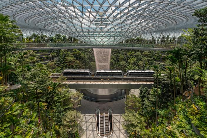 """Safdie Architects—the masterminds behind the seminal Marina Bay Sands Singapore—pioneered the eco-friendly vision of the <a href=""""https://www.architecturaldigest.com/story/moshe-safdie-singapores-jewel-changi-airport?mbid=synd_yahoo_rss"""" rel=""""nofollow noopener"""" target=""""_blank"""" data-ylk=""""slk:Changi Airport"""" class=""""link rapid-noclick-resp"""">Changi Airport</a>. The main highlight is the Jewel Changi, a revolutionary garden terminal with the world's tallest indoor waterfall thundering from the top of the toroidal structure's steel dome. The Rain Vortex is the centerpiece of the Shiseido Forest Valley, a five-story greenhouse of living walls. On the upper level is Canopy Park, a 13,000-square-meter complex of gardens, walking trails, playgrounds, and an animal topiary. It will also have 280 shops, restaurants, and a hotel."""