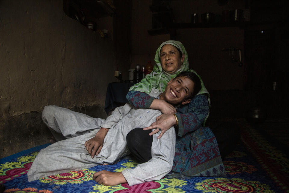"""Kashmiri woman Zamrooda with her son Sahil Majeed whom she saved from a leopard attack in 2009 in Srinagar, Indian controlled Kashmir, Thursday, Sept. 10, 2020. Zamrooda said despite her wounds and continuous bleeding she fought with leopard and dragged her son Sahil majeed from the mouth of a leopard as he attacked them in their village in 2009. """" I had finished almost all work at my home. I supposed to go in fields for work. I saw something strange animal he jumped on me I was not able to move I was bleeding he tore my clothes suddenly it comes to my mind that my son was outside I ran away towards my son I hit leopard's mouth with stick and pull my son out from his mouth. He escaped and entered others cow shed where he killed a cow. Then I was shifted to hospital by locals for treatment. my son was 4 years old that time."""" (AP Photo/Mukhtar Khan)"""