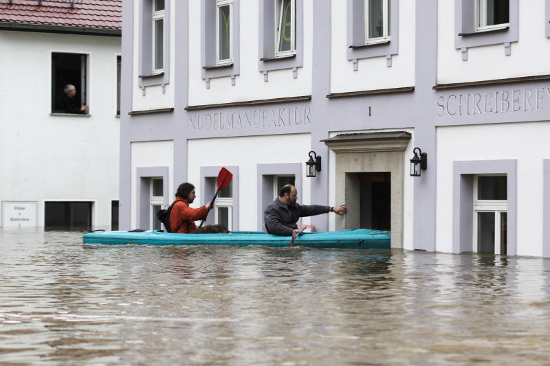 Two men in a boat paddle over the flooded market place of the city of Wehlen at the river Elbe in , Germany, Tuesday, June 4, 2013. After heavy rainfalls, swollen rivers flooded areas in Germany, Austria , Switzerland and Czech Republic. (AP Photo/Markus Schreiber)