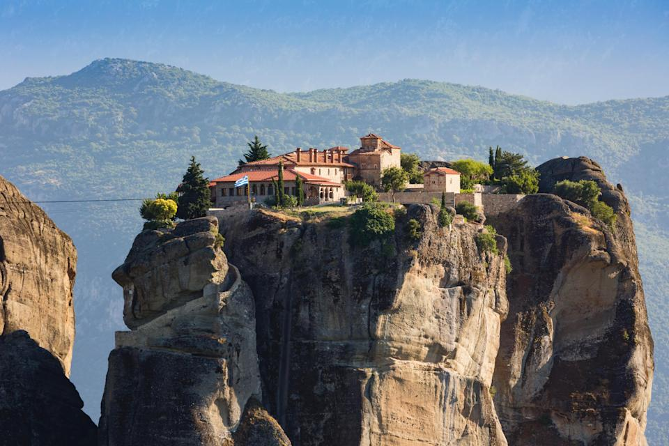 """Though Meteora isn't name-recognizable like the <a href=""""https://www.cntraveler.com/activities/paris/cathedrale-notre-dame-de-paris?mbid=synd_yahoo_rss"""" rel=""""nofollow noopener"""" target=""""_blank"""" data-ylk=""""slk:Notre Dames"""" class=""""link rapid-noclick-resp"""">Notre Dames</a> of the world, you've likely seen images of these mountain-top monasteries before. The set of stone buildings are set atop steep, jagged cliffs in Central Greece, creating a scene seemingly out of a fairytale. Eastern Orthodox monks first occupied the region's caves in the 11th century, before the monasteries were even built. Now, after a thousand-year history of much turmoil—including Turkish invasion, the creation of the complex and its frescoes, and efforts to use it as a refuge from the Ottoman Empire—six of the 24 of the monasteries remain active. The Ypapanti monastery is usually open to the public, and well worth the four-and-a-half hour train ride from Athens."""