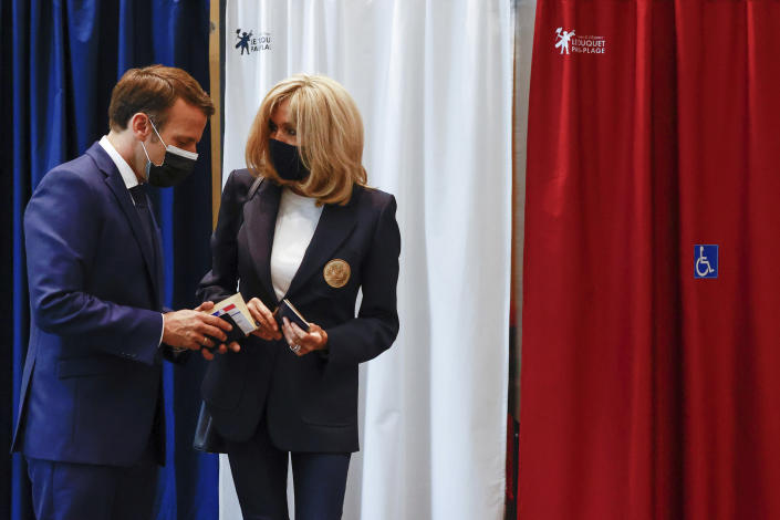 French President Emmanuel Macron chats with his wife Brigitte during the first round of French regional and departmental elections, in Le Touquet-Paris-Plage, northern France, Sunday, June 20, 2021. The elections for leadership councils of France's 13 regions, from Brittany to Burgundy to the French Riviera, are primarily about local issues like transportation, schools and infrastructure. But leading politicians are using them as a platform to test ideas and win followers ahead of the April presidential election. (Christian Hartmann/Pool via AP)