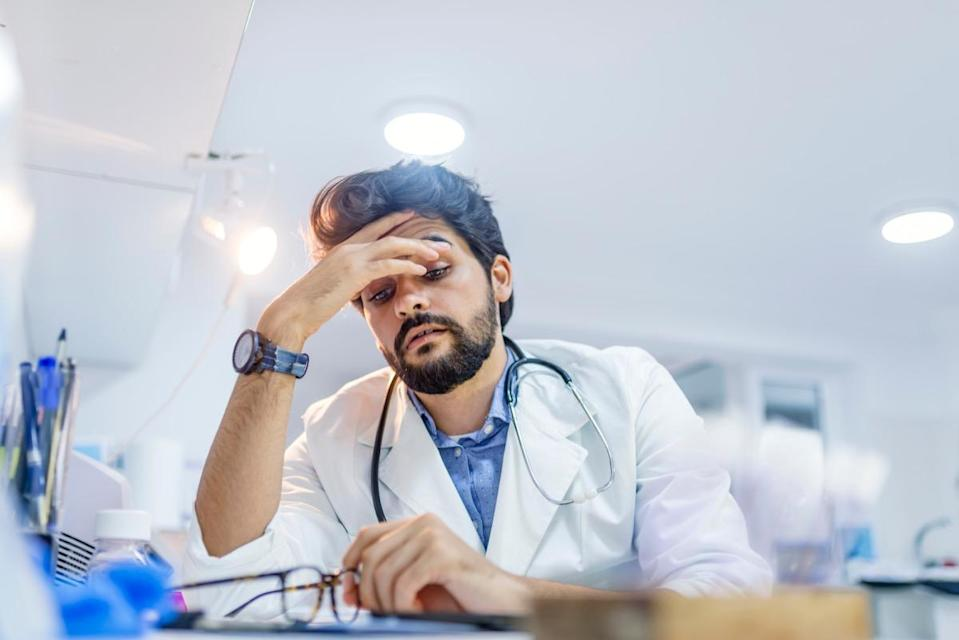Stressed male doctor sat at his desk. Mid adult male doctor working long hours. Overworked doctor in his office. Not even doctors are exempt from burnout