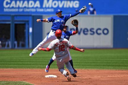 May 24, 2018; Toronto, Ontario, CAN; Los Angeles Angels catcher Martin Maldonado (12) slides safely into second as Toronto Blue Jays infield Gio Urshela (3) jumps for a wide throw from first base during the regular season MLB game between the Los Angeles Angels and Toronto Blue Jays at Rogers Centre. Mandatory Credit: Gerry Angus-USA TODAY Sports