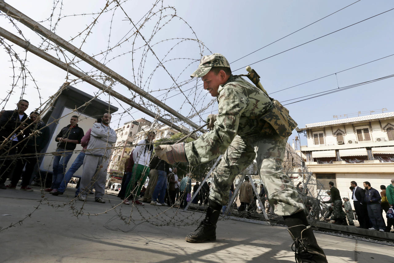 An Egyptian Army soldier lays barbed wire near the presidential palace to secure the site of overnight clashes between supporters and opponents of President Mohammed Morsi in Cairo, Egypt, Thursday, Dec. 6, 2012. The Egyptian army has deployed tanks outside the presidential palace in Cairo following clashes between supporters and opponents of Mohammed Morsi that left several people dead and hundreds wounded. (AP Photo/Hassan Ammar)