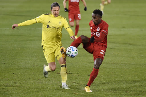 Toronto FC's Richie Laryea, right, controls the ball as Nashville SC's Alex Muyl defends during the first half of an MLS soccer playoff match Tuesday, Nov. 24, 2020, in East Hartford, Conn. (AP Photo/Jessica Hill)