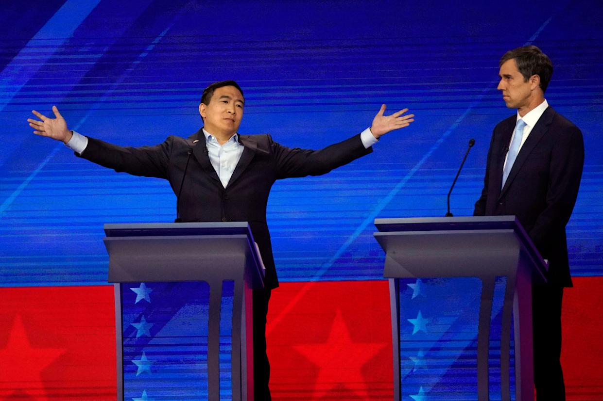 Former Texas Rep. Beto O'Rourke, right, listens to Andrew Yang, left, Thursday, Sept. 12, 2019, during a Democratic presidential primary debate hosted by ABC at Texas Southern University in Houston.