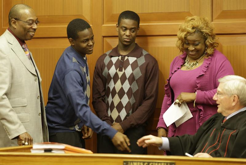 "Jamal Byers, left center, shakes hands with Judge James Cissell, right, after Jamal and Tyshawn Byers, right center, were adopted by the Rev. Edward Byers, left, and his wife Darnette Byers, Friday, Nov. 22, 2013, in Cincinnati. ""I know what it's like to move from house to house,"" said Tyshawn. He can empathize with a 9-year-old Ohio boy was recently given to child welfare officials by adoptive parents who raised him from infancy, but who have since been charged with abandoning him.(AP Photo/Al Behrman)"