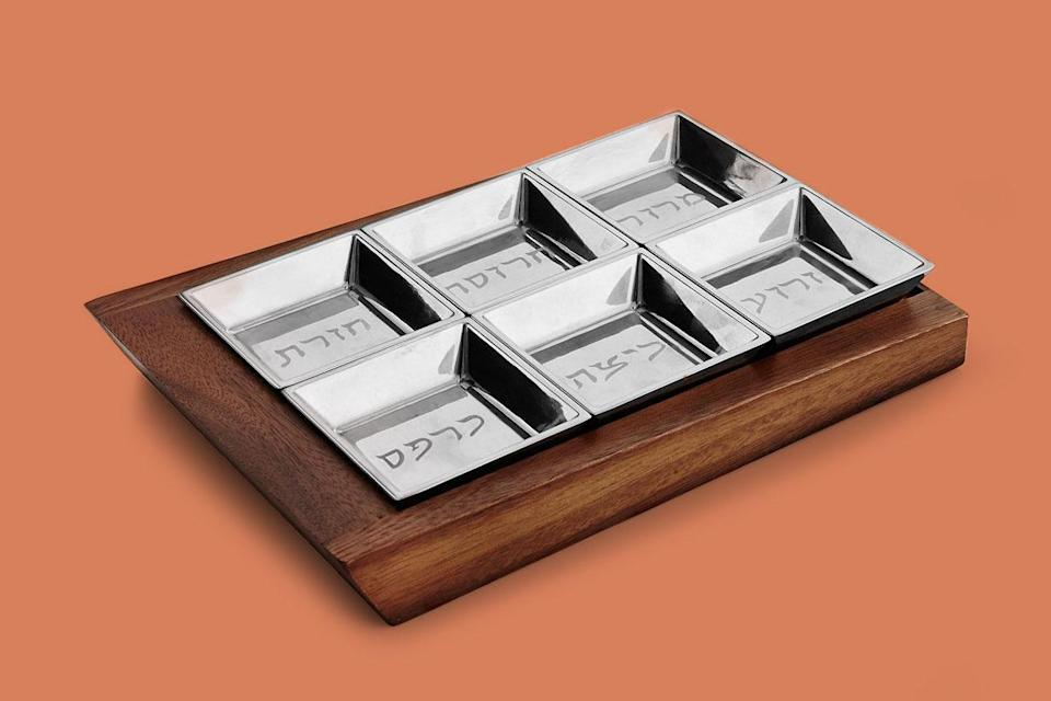 """<p>Wood and alloy come together in a geometric design with each bowl labeled in both English and Hebrew of the symbolic Seder foods.</p> <p><em><strong>Shop Now: </strong>Nambé Geo Seder Plate, $160, <a href=""""https://click.linksynergy.com/deeplink?id=93xLBvPhAeE&mid=3184&murl=https%3A%2F%2Fwww.macys.com%2Fshop%2Fproduct%2Fnambe-geo-seder-plate%3FID%3D8918119&u1=MSL10PassoverSederPlatesGuaranteedtoBecomeYourNextFamilyHeirloomachurchiPasGal8067612202103I"""" rel=""""sponsored noopener"""" target=""""_blank"""" data-ylk=""""slk:macys.com"""" class=""""link rapid-noclick-resp"""">macys.com</a>.</em></p>"""
