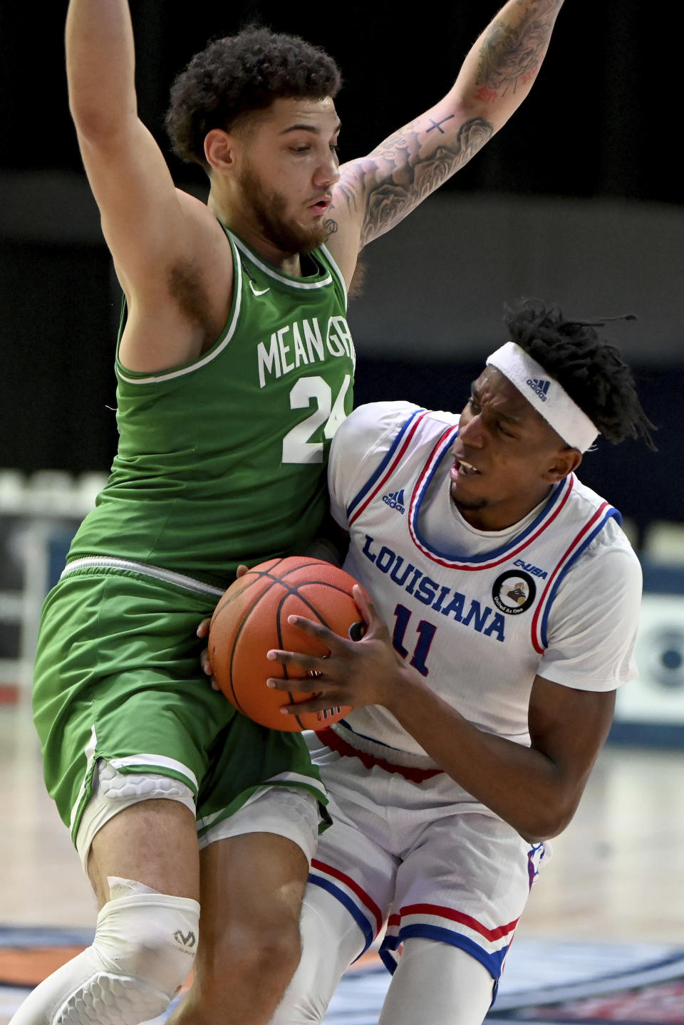 Louisiana Tech guard JaColby Pemberton (11) tries to drive against North Texas forward Zachary Simmons (24) in the second half of an NCAA college basketball game in the Conference USA men's tournament, in Frisco, Texas, Friday, March 12, 2021. (AP Photo/Matt Strasen)