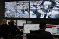 Police and traffic warden employees monitor screens showing the flow of people and web cameras at a police station, in Venice, Italy, Thursday, June 17, 2021. After a 15-month pause in mass international travel, Venetians are contemplating how to welcome visitors back to the picture-postcard canals and Byzantine backdrops without suffering the indignities of crowds clogging its narrow alleyways, day-trippers perched on stoops to imbibe a panino and hordes of selfie-takers straining for a spot on the Rialto Bridge or in front of St. Mark's Basilica. (AP Photo/Luca Bruno)