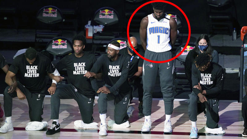Jonathan Isaac is pictured standing during the national anthem, while his teammates can be seen alongside taking a knee in protest.