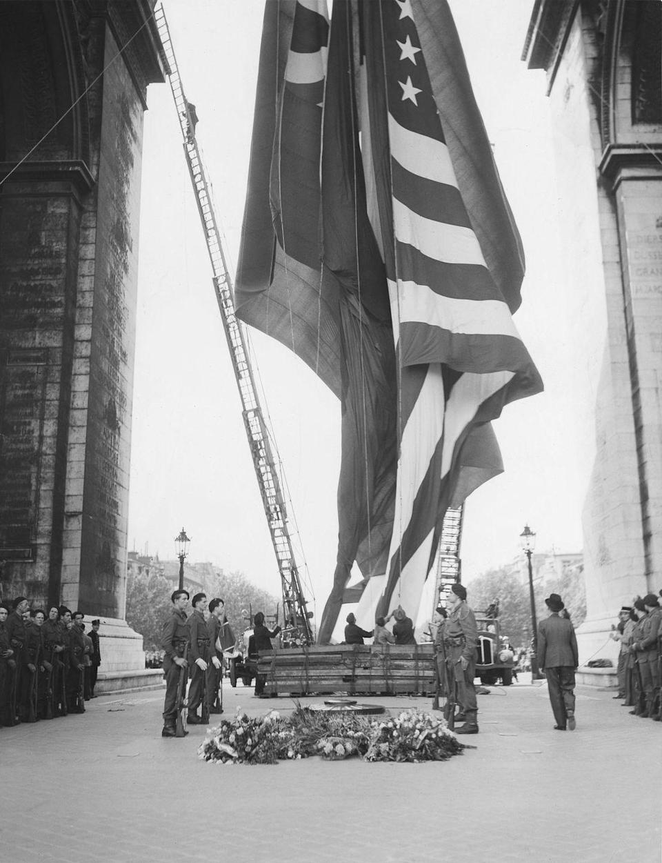 <p>The flags of Russia, France, China, Great Britain, and the United States are hoisted inside Paris' famous Arc de Triomphe following the surrender announcement.</p>