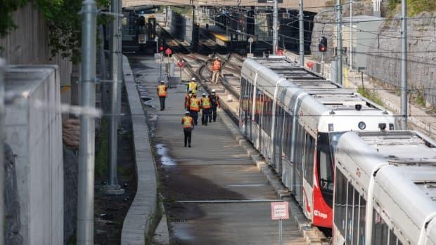 Crews walk along the Confederation Line in Ottawa one day after the axle of this out-of-service LRT train dislodged from the rail.  (Alexander Behne/CBC - image credit)
