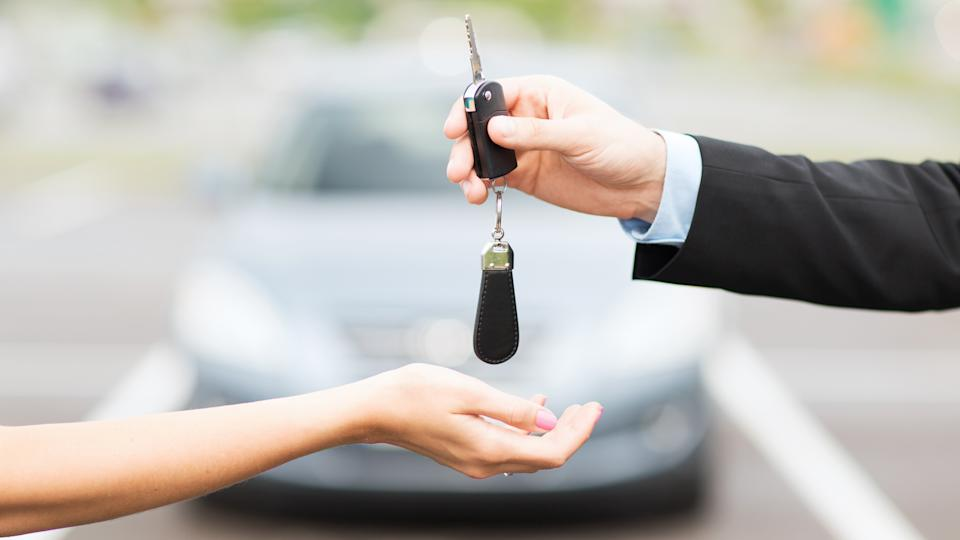 transportation, business, rent and ownership concept - close up of customer and salesman hands with car key outside.