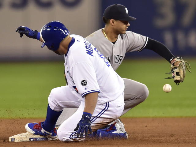 New York Yankees second baseman Gleyber Torres (25) can't make the catch as Toronto Blue Jays' Kendrys Morales (8) slides into second base after hitting a double during the 13th inning of a baseball game Wednesday, June 6, 2018, in Toronto. (Frank Gunn/The Canadian Press via AP)