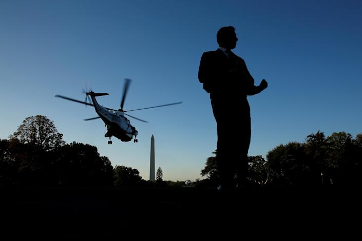 <p>Gusts kicked up by the rotors of the Marine One helicopter buffet a Secret Service agent as President Donald Trump and first lady Melania Trump depart for travel to Las Vegas, in the aftermath of the shooting there, from the South Lawn of the White House in Washington, Oct. 4, 2017. (Photo: Jonathan Ernst/Reuters) </p>