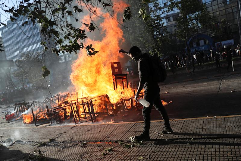 A demonstrator tosses a chair into an improvised bonfire during an anti-government protest in Santiago, Chile on Oct. 28, 2019. (Photo: Edgard Garrido/Reuters)