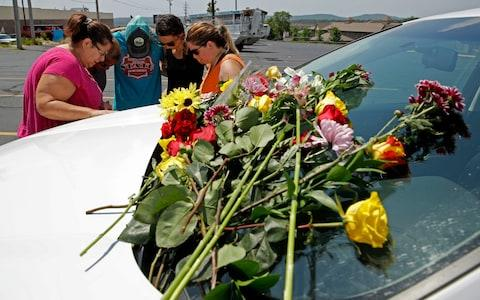 People pray next to a car believed to belong to a victim of the duck boat accident - Credit:  Charlie Riedel/AP
