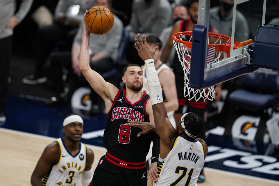 Chicago Bulls guard Zach LaVine (8) dunks over Indiana Pacers guard Kelan Martin (21) during the second half of an NBA basketball game in Indianapolis, Tuesday, April 6, 2021. (AP Photo/Michael Conroy)