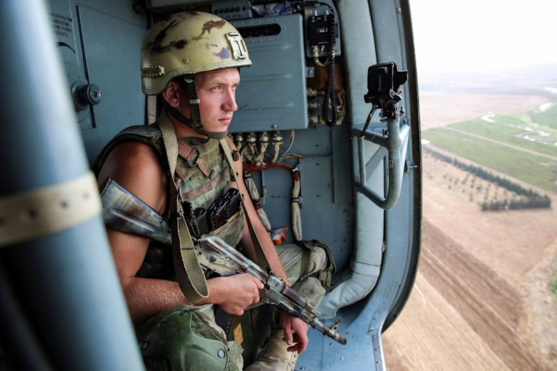 A picture taken during a press tour provided by the Russian Armed Forces on September 15, 2017 shows a Russian soldier riding in a helicopter en route to the eastern Syrian city of Deir Ezzor (AFP Photo/Dominique DERDA)