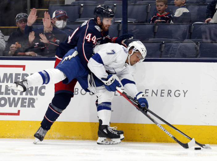 Columbus Blue Jackets defenseman Vladislav Gavrikov, left, grabs Tampa Bay Lightning forward Mathieu Joseph during the second period of an NHL hockey game in Columbus, Ohio, Thursday, April 8, 2021. (AP Photo/Paul Vernon)