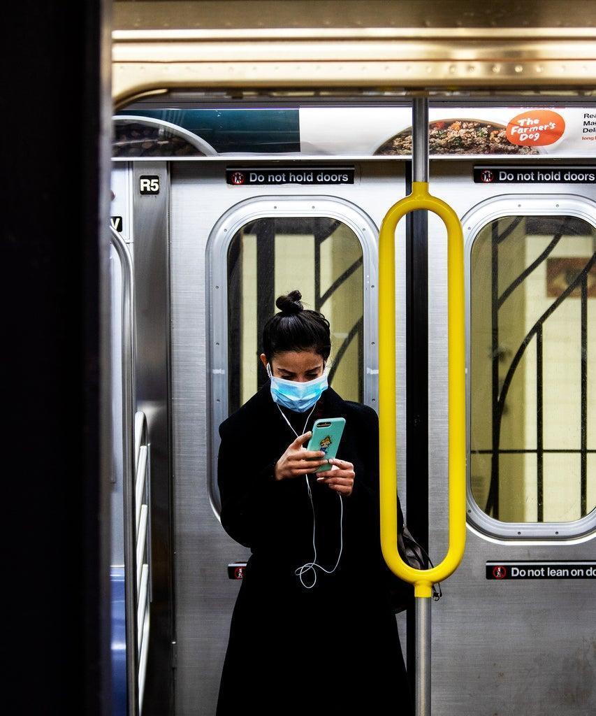 A commuter wears a protective mask while riding a subway in New York, U.S., on Tuesday, March 17, 2020. In New York City, the virtual shutdown from the coronavirus pandemic is threatening to create massive holes in the budget as billions of dollars in tax revenue disappears. Photographer: Demetrius Freeman/Bloomberg via Getty Images